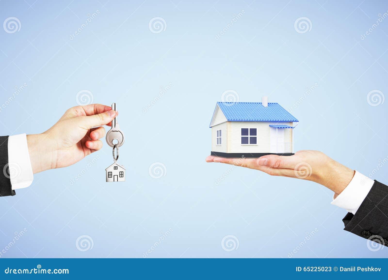 Nieruchomości pojęcie z mężczyzna ręką z kluczem i domem w inny