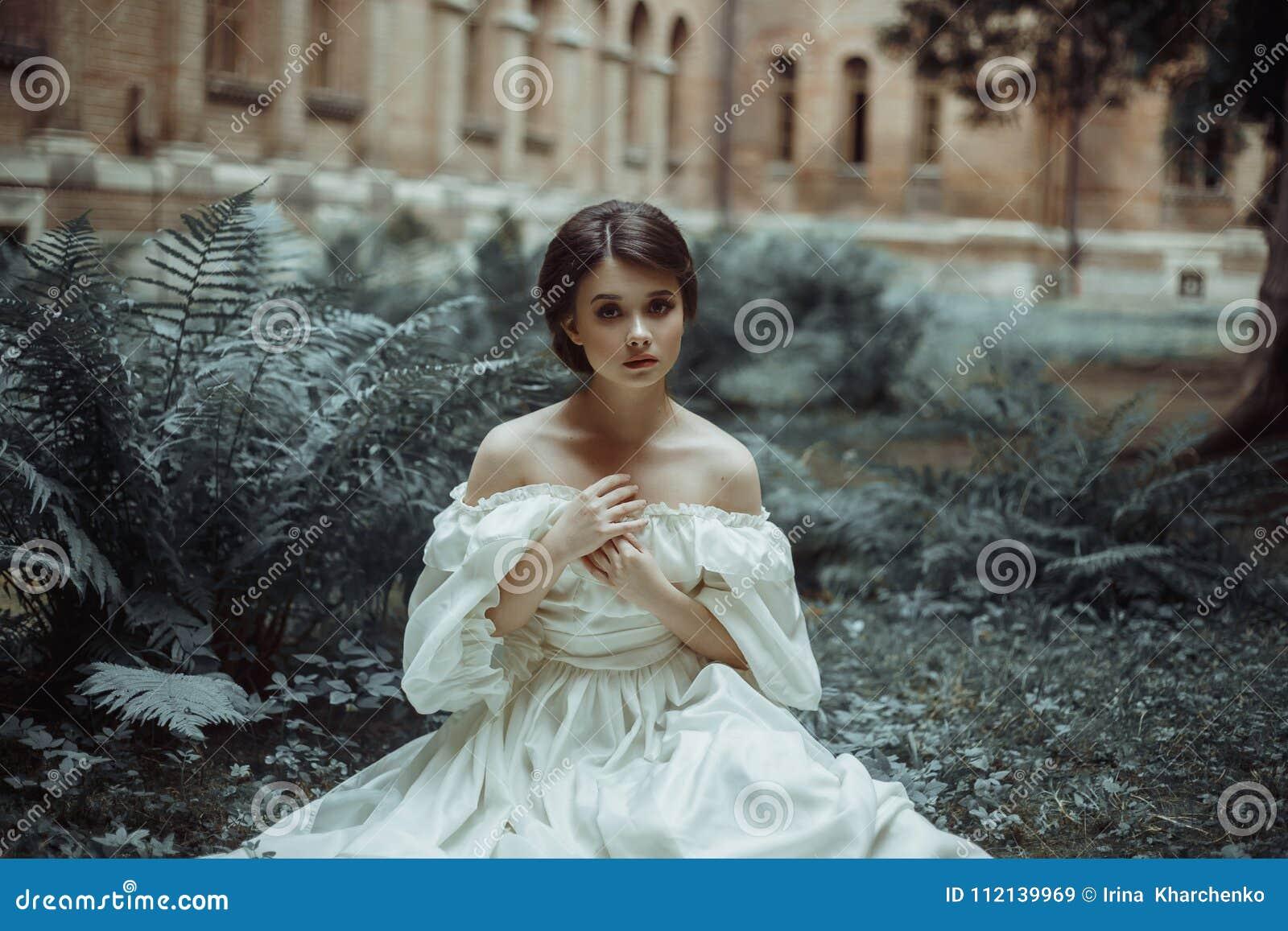 Niesamowicie piękny princess siedzi w grodowym ogródzie wśród mech i paproci Piękna, przelękła twarz, Duży smutny
