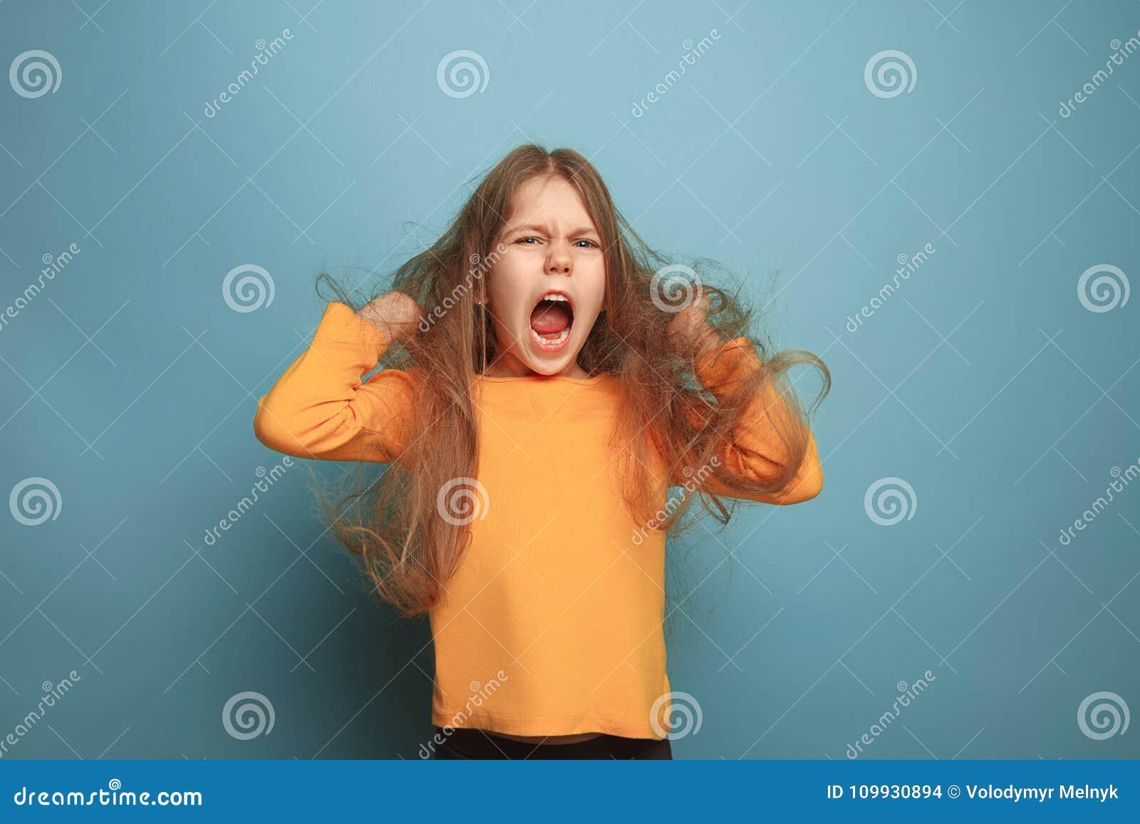 Niespodzianka Nastoletnia dziewczyna na błękitnym tle Wyrazy twarzy i ludzie emoci pojęcia