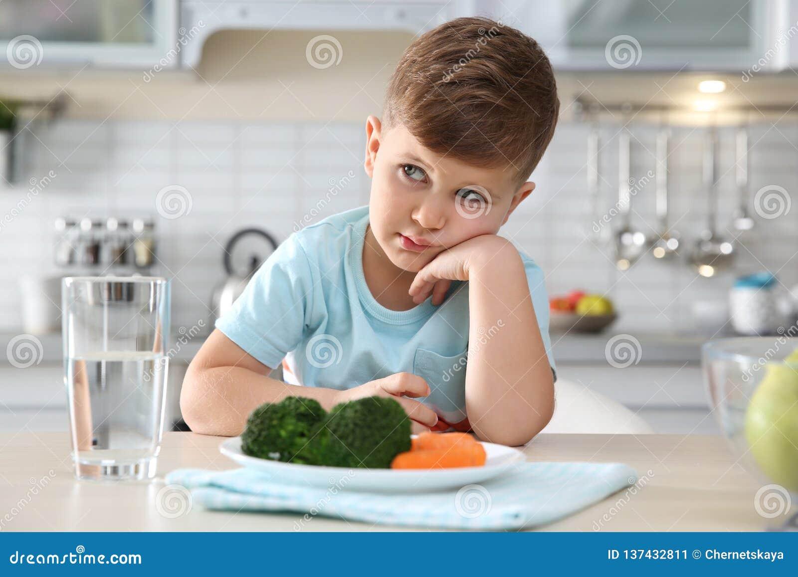 Nieszczęśliwa chłopiec z talerzem warzywa przy stołem