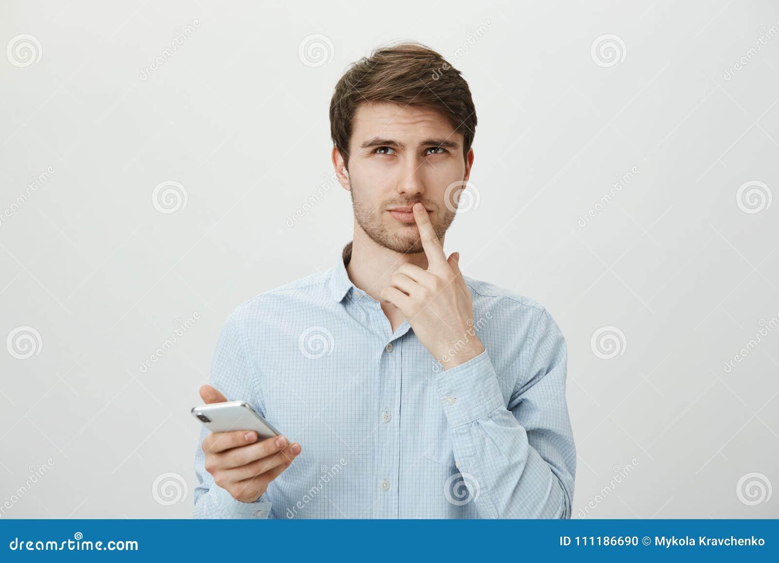 Of niet doen, nemend besluiten is harde taak Aantrekkelijk ongeschoren mannetje in formele smartphone van de overhemdsholding ter