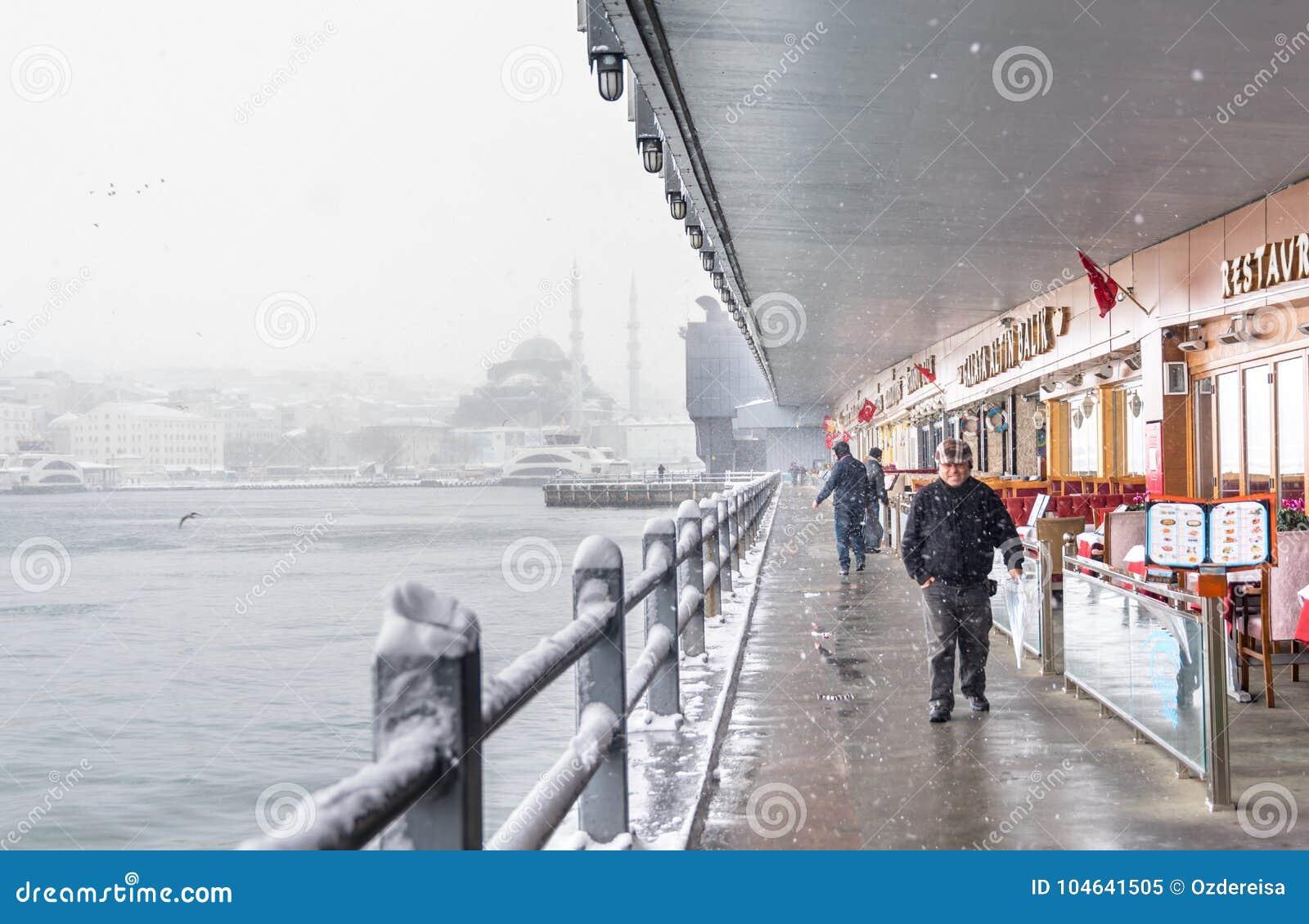 Niet geïdentificeerde mens die onder de galatabrug lopen op een sneeuwdag in de winter