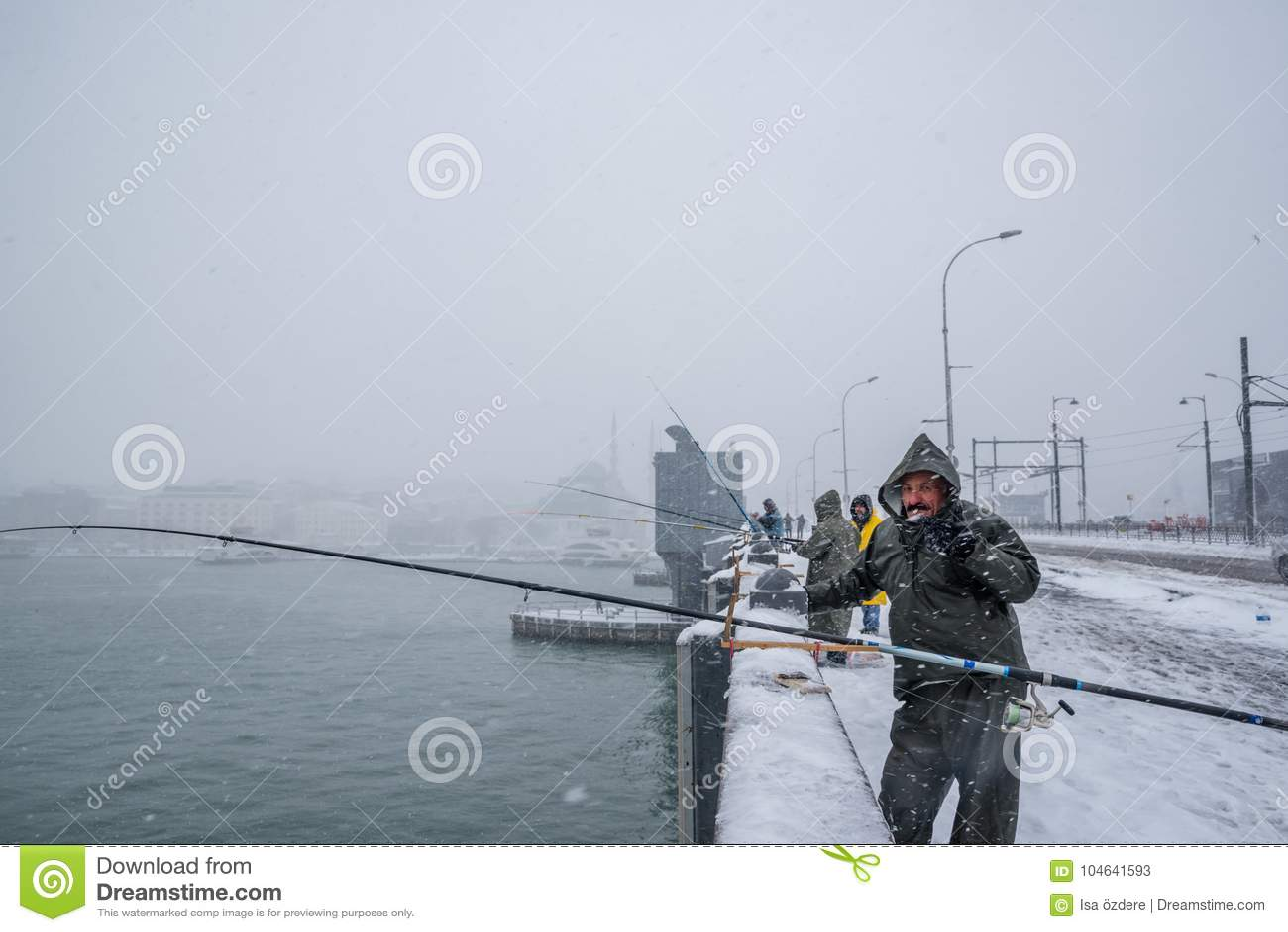 Niet geïdentificeerde mens die op de galatabrug vissen op een sneeuwdag in de winter