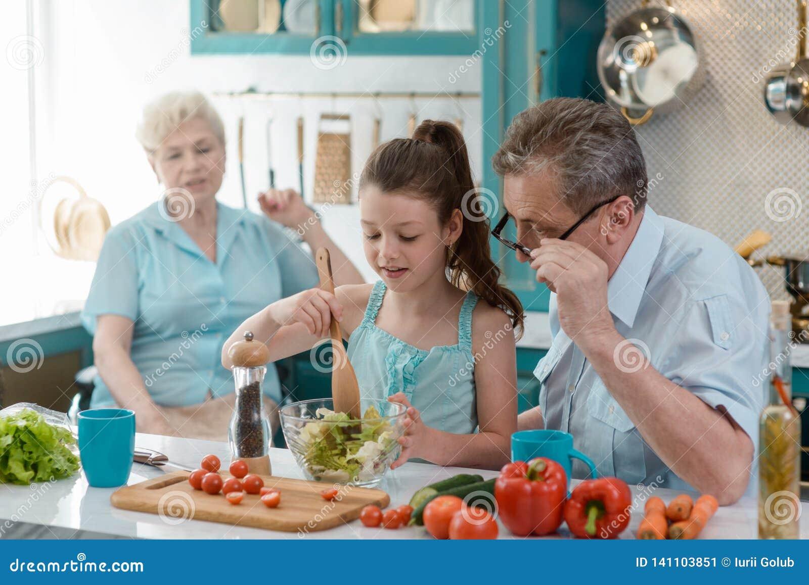 Nieta de enseñanza del abuelo a cocinar