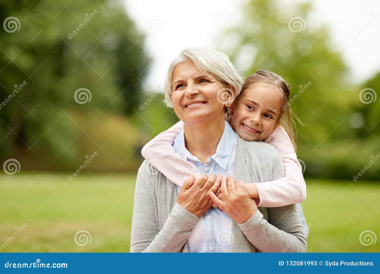 Nieta que abraza a la abuela en el parque del verano