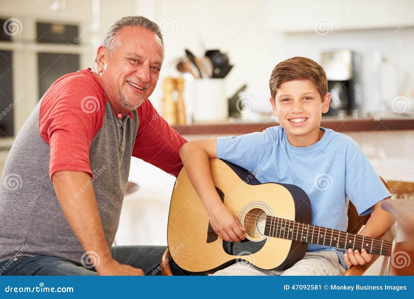 Nieto de enseñanza de abuelo para tocar la guitarra