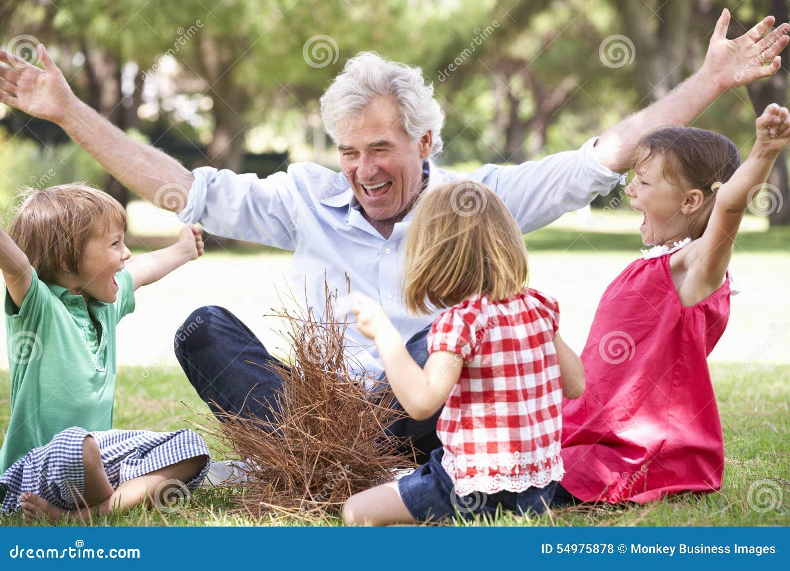 Nietos de enseñanza del abuelo para construir el fuego del campo