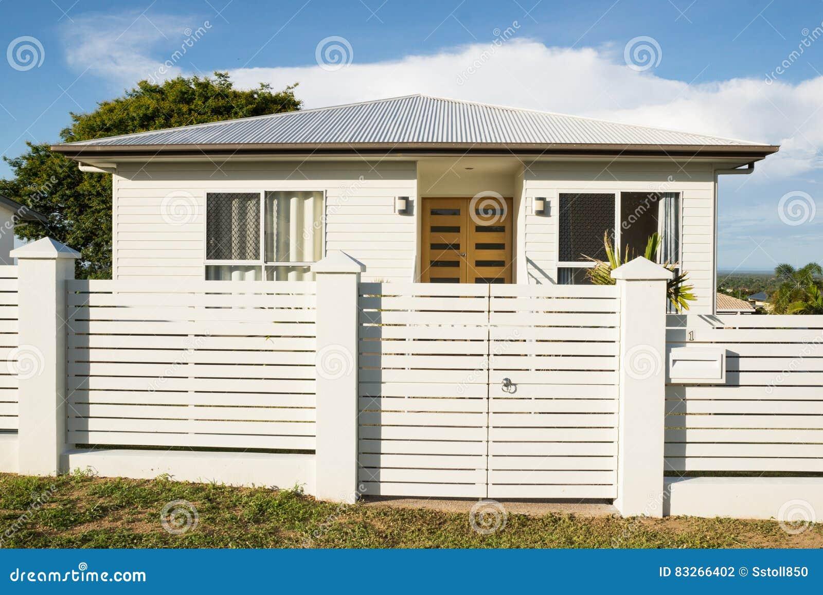 Nieuw modern eigentijds huis buiten met omheining en voordeur stock
