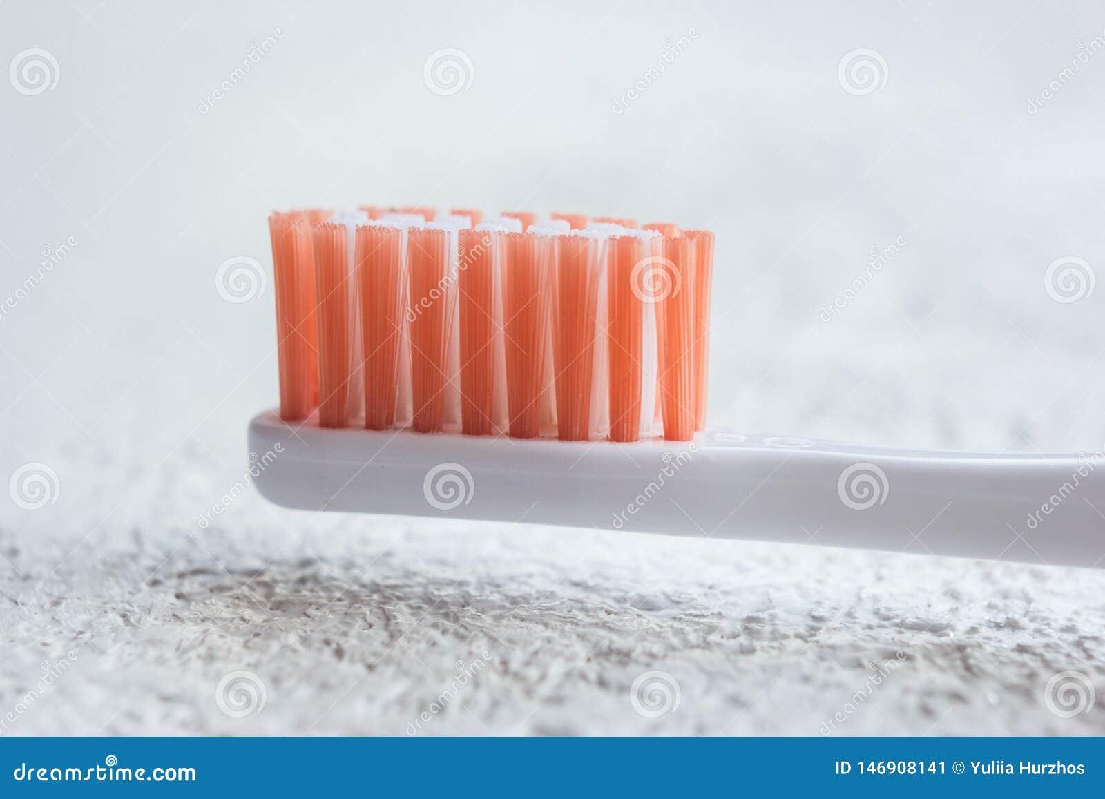 Nieuw oranje-overeind gezet tandenborstel hoofdclose-up op een witte lijst onderwerp van het persoonlijke close-up van het hygiën
