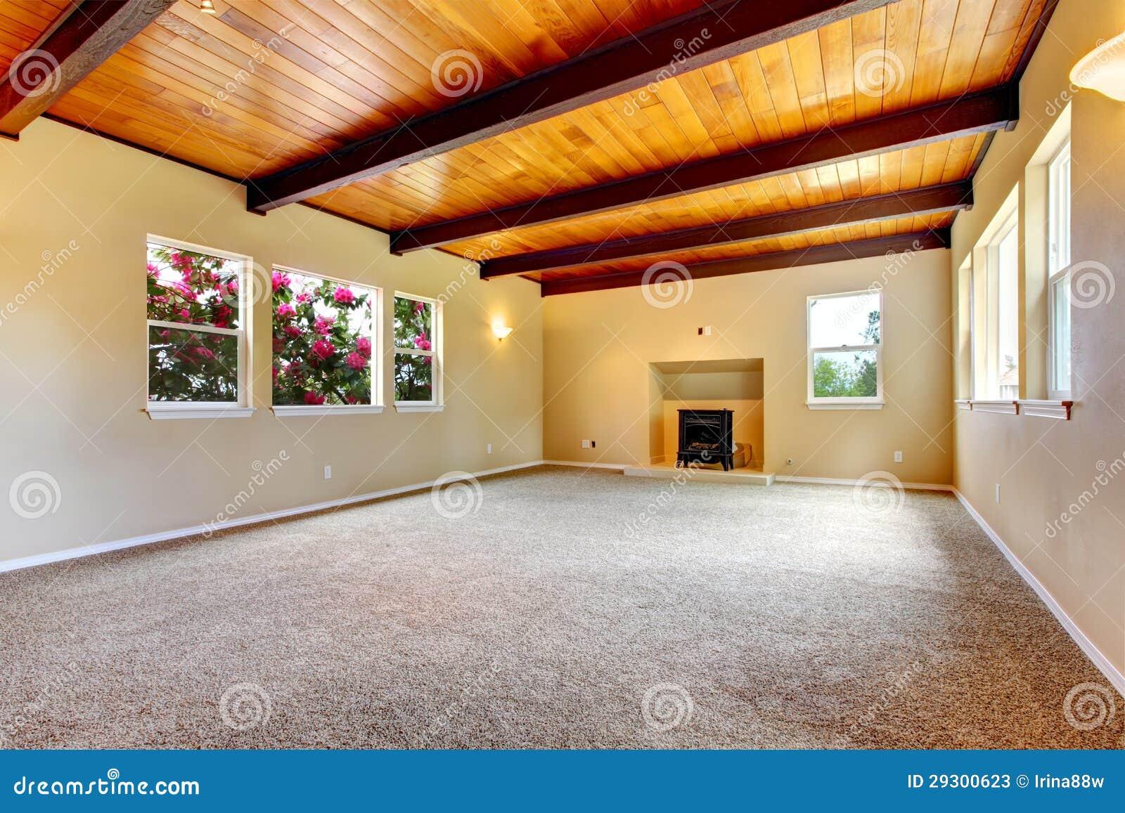Nieuwe grote lege woonkamer met houten plafond en open haard ...