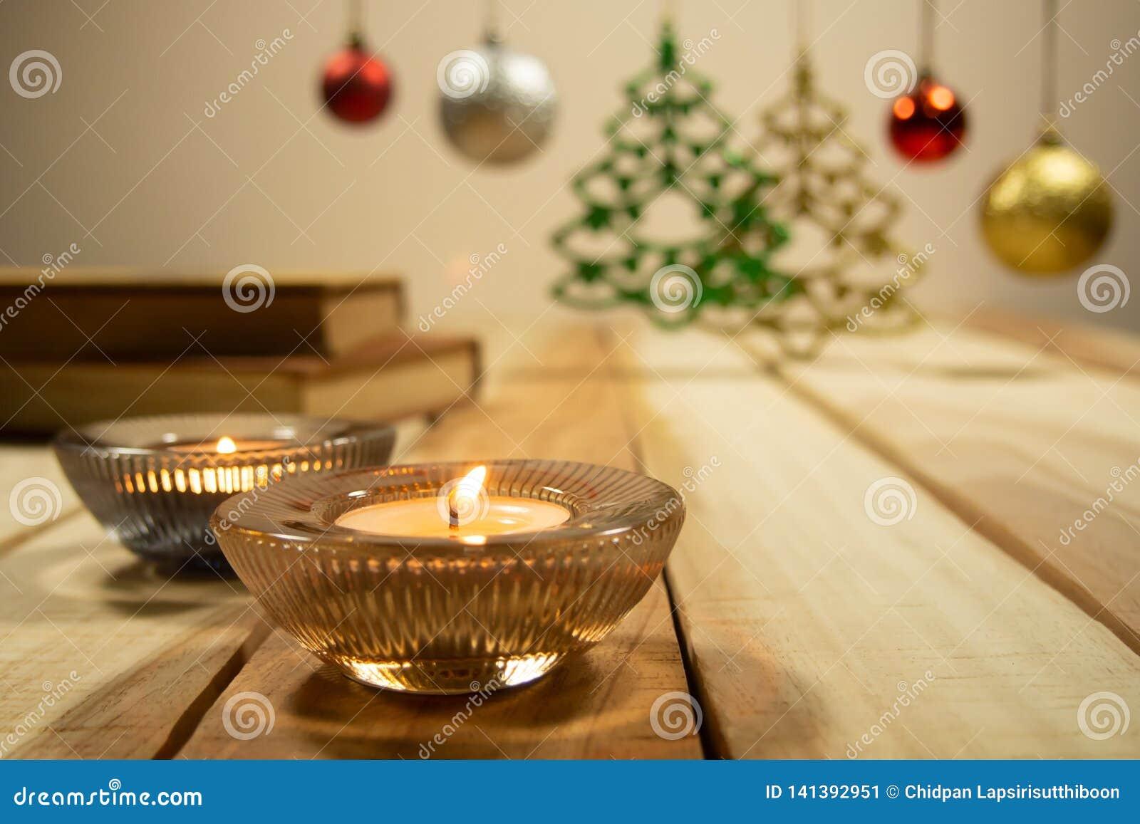 Nieuwe jaar en van Kerstmissamenstellingen achtergrond met aromakaars, boeken en de bal van decoratiekerstmis op de houten lijst