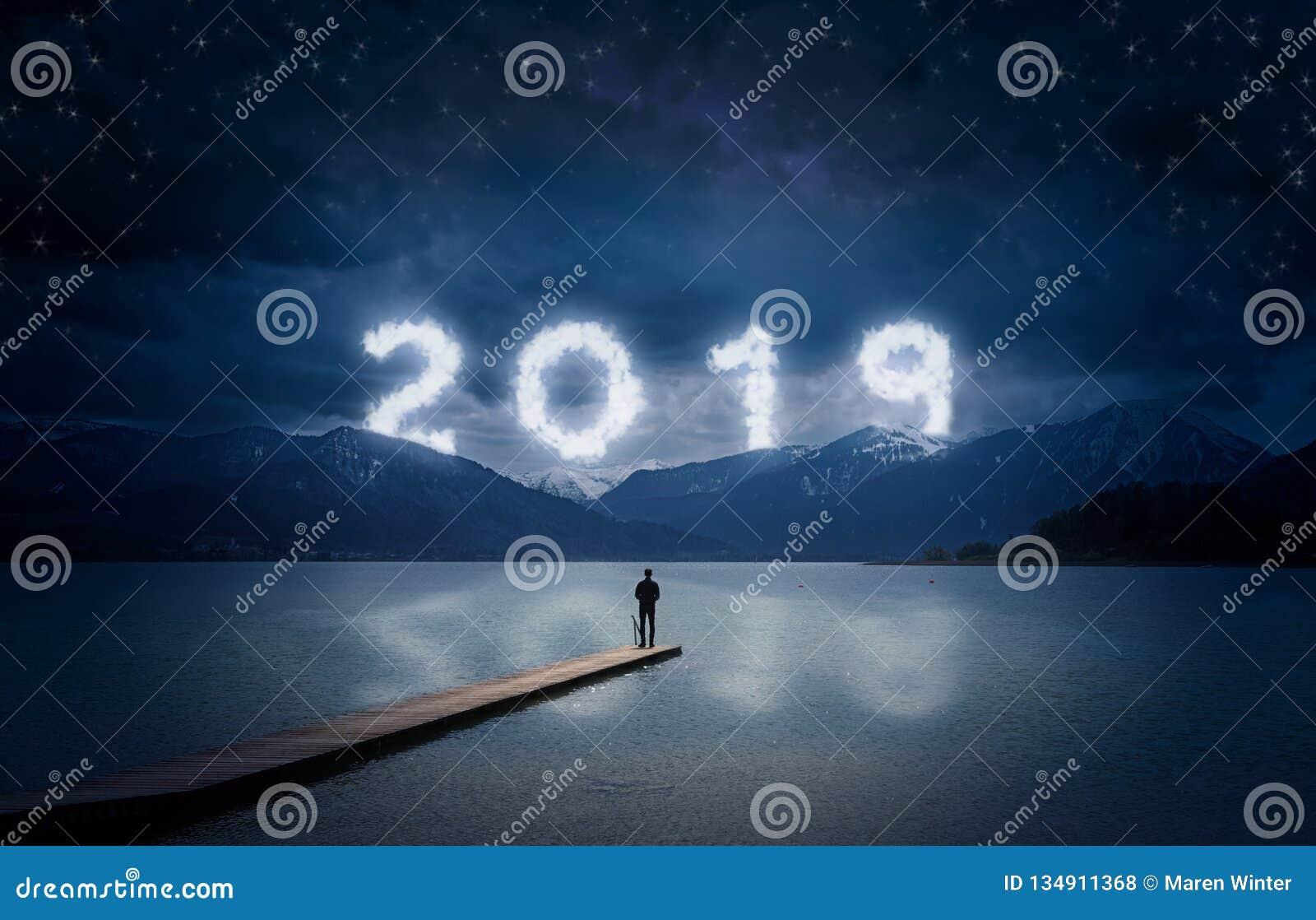 Nieuwe jaarachtergrond, jonge mens die zich op een pier in een meer bevinden en aan de bergen onder de donkere hemel met bewolkte