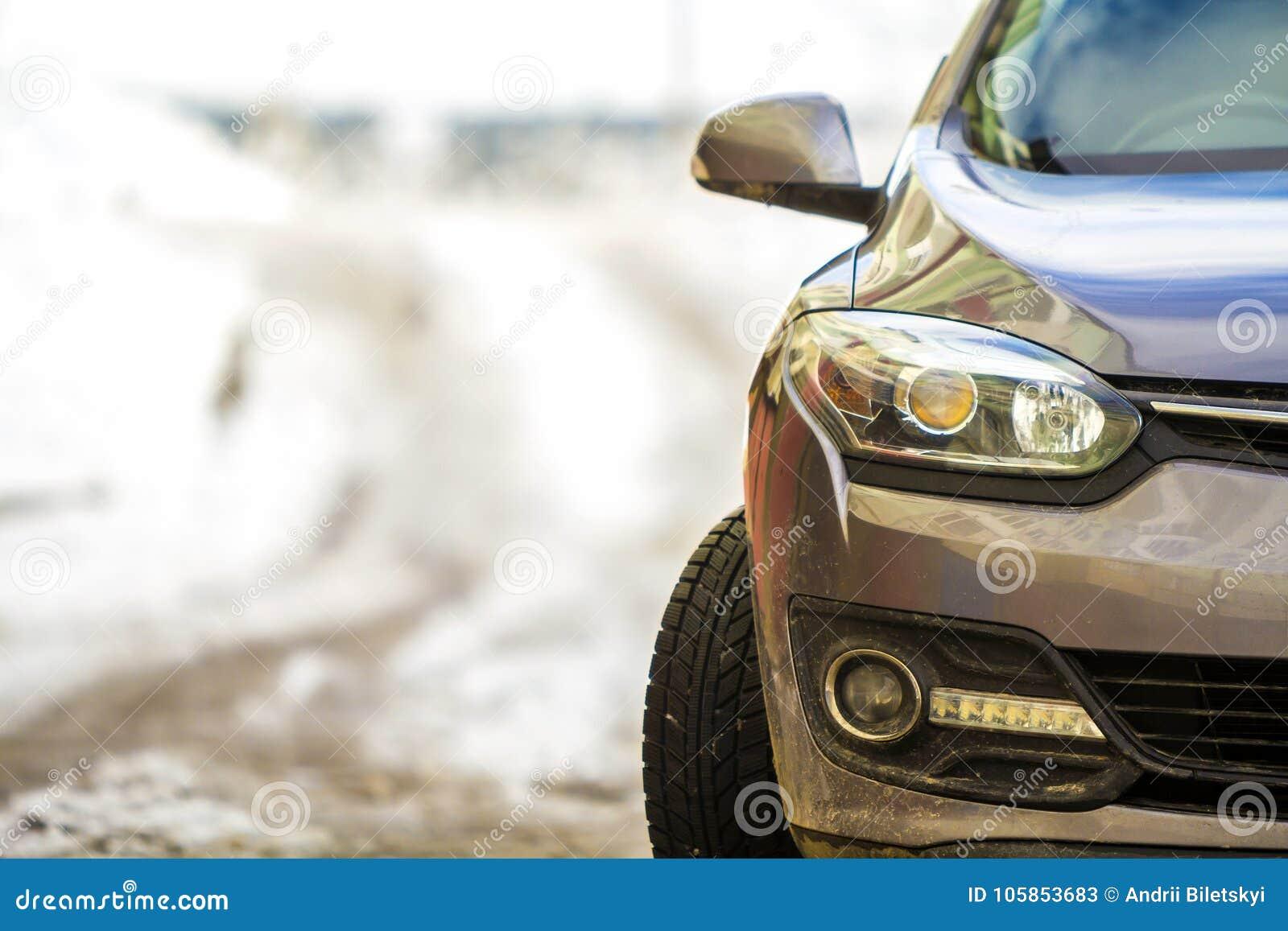Nieuwe moderne grijze die auto op een straat in de winter wordt geparkeerd