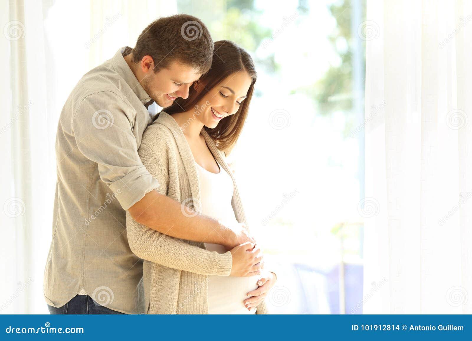 Nieuwe ouders die buik van zwangere moeder bekijken