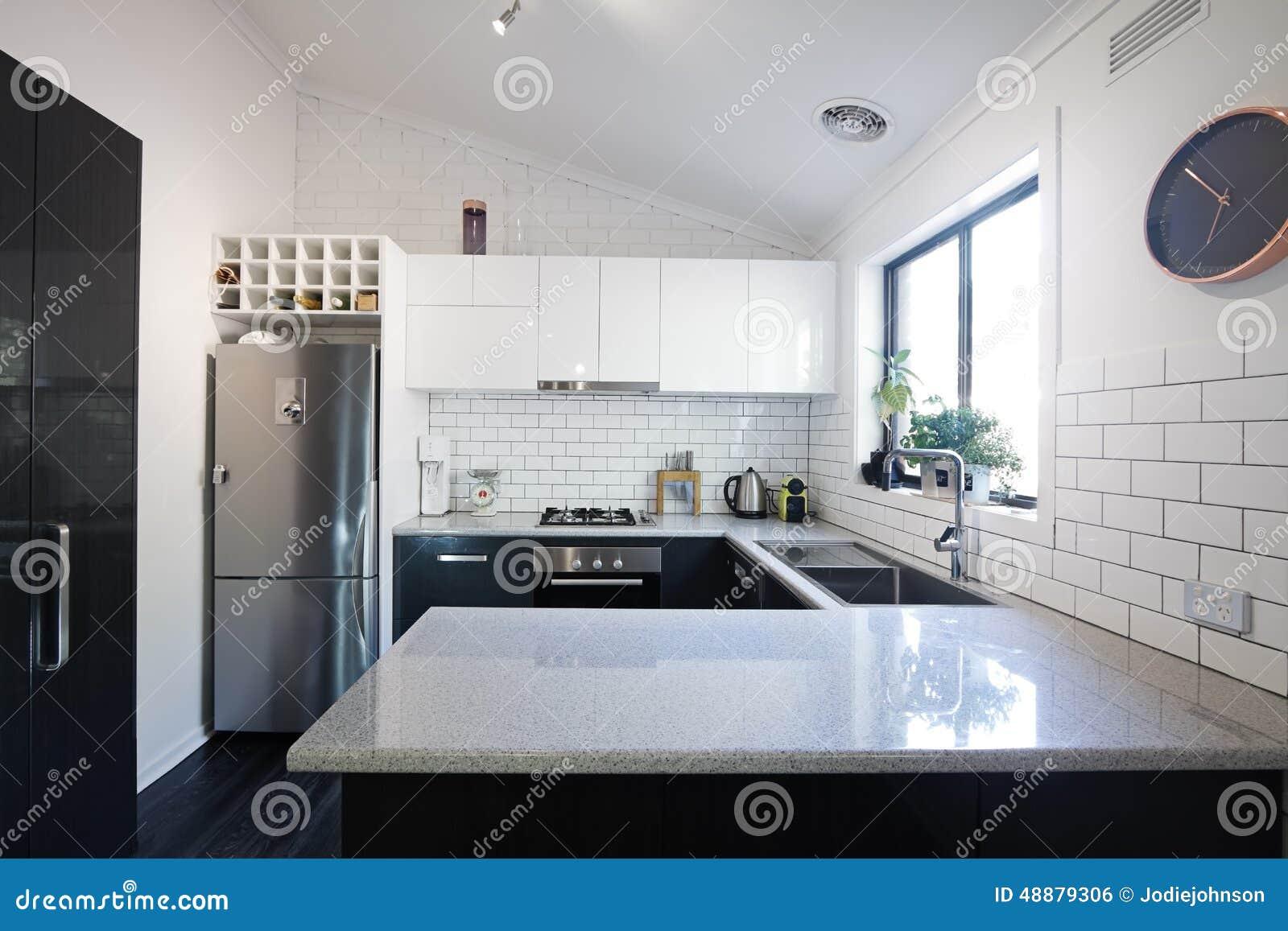 Nieuwe zwart witte eigentijdse keuken met metrotegels stock foto