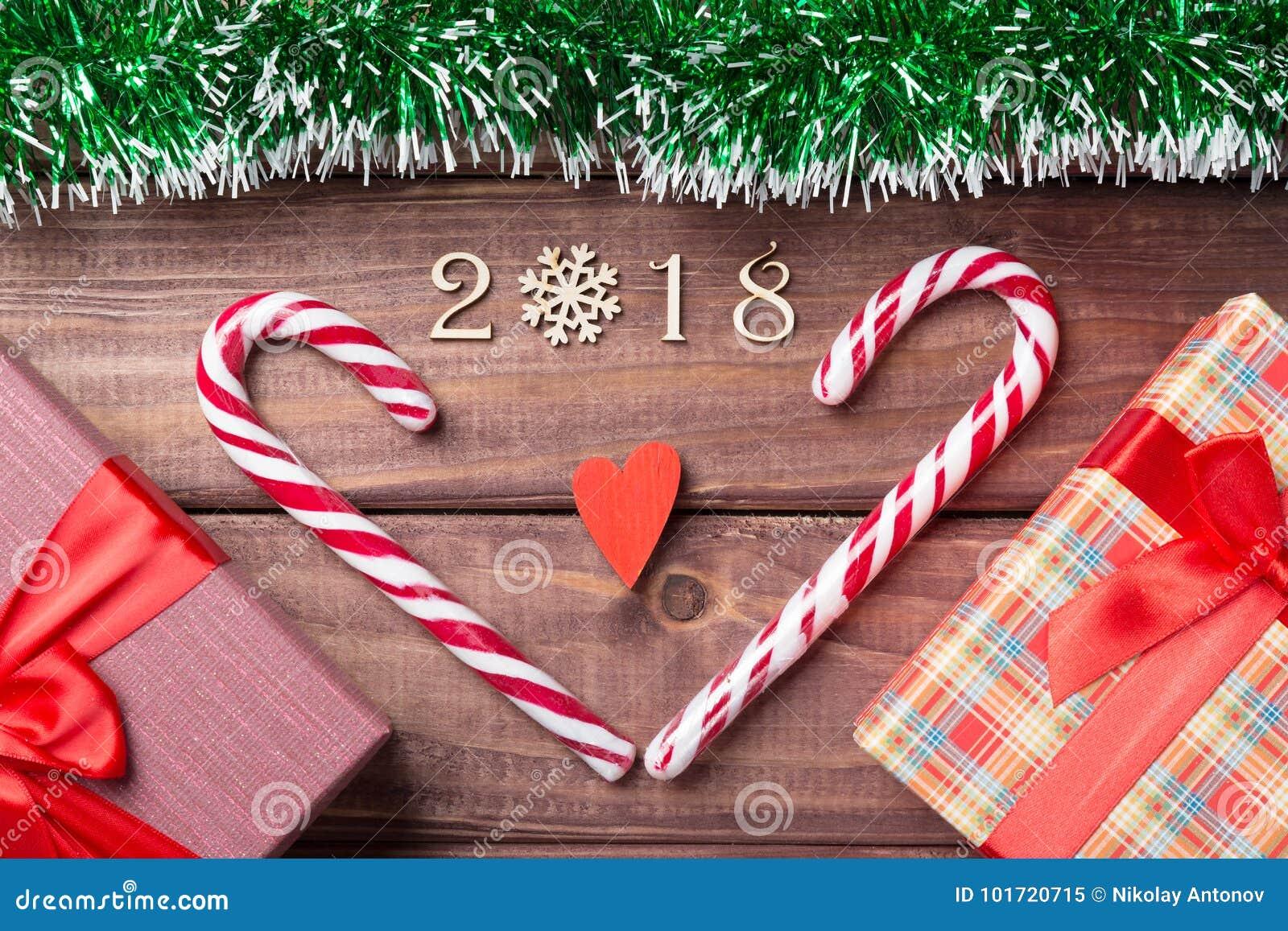 Nieuwjaar of Kerstkaart de houten decoratieve waarden van 2018 met hart gevormd suikergoedriet, giftboxes en rood hart met groene