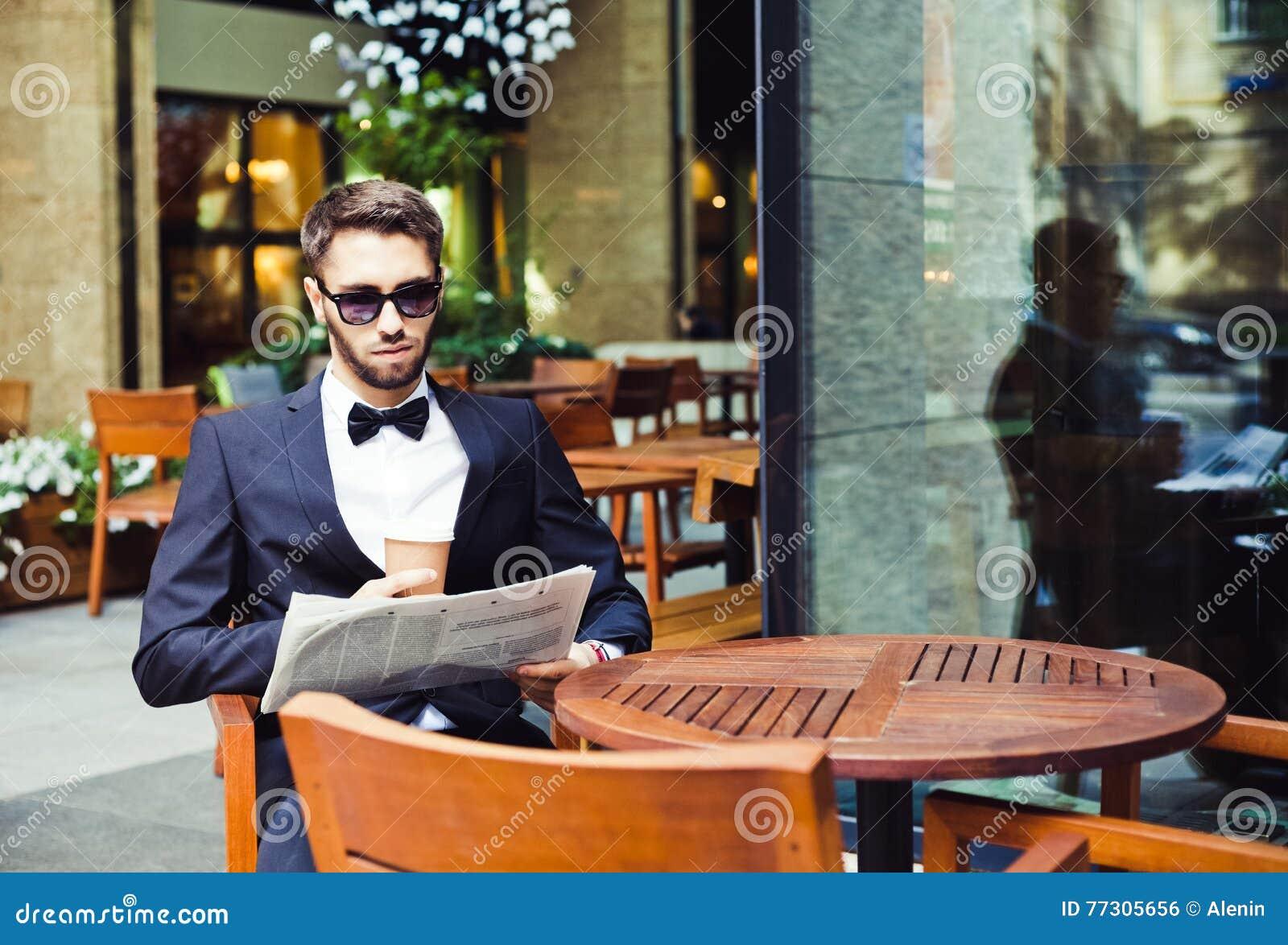 Nieuws en Koffie Jonge zakenman die het ochtenddocument lezen, drinkend koffie in een gebouw van het koffiebureau Zoete croissant