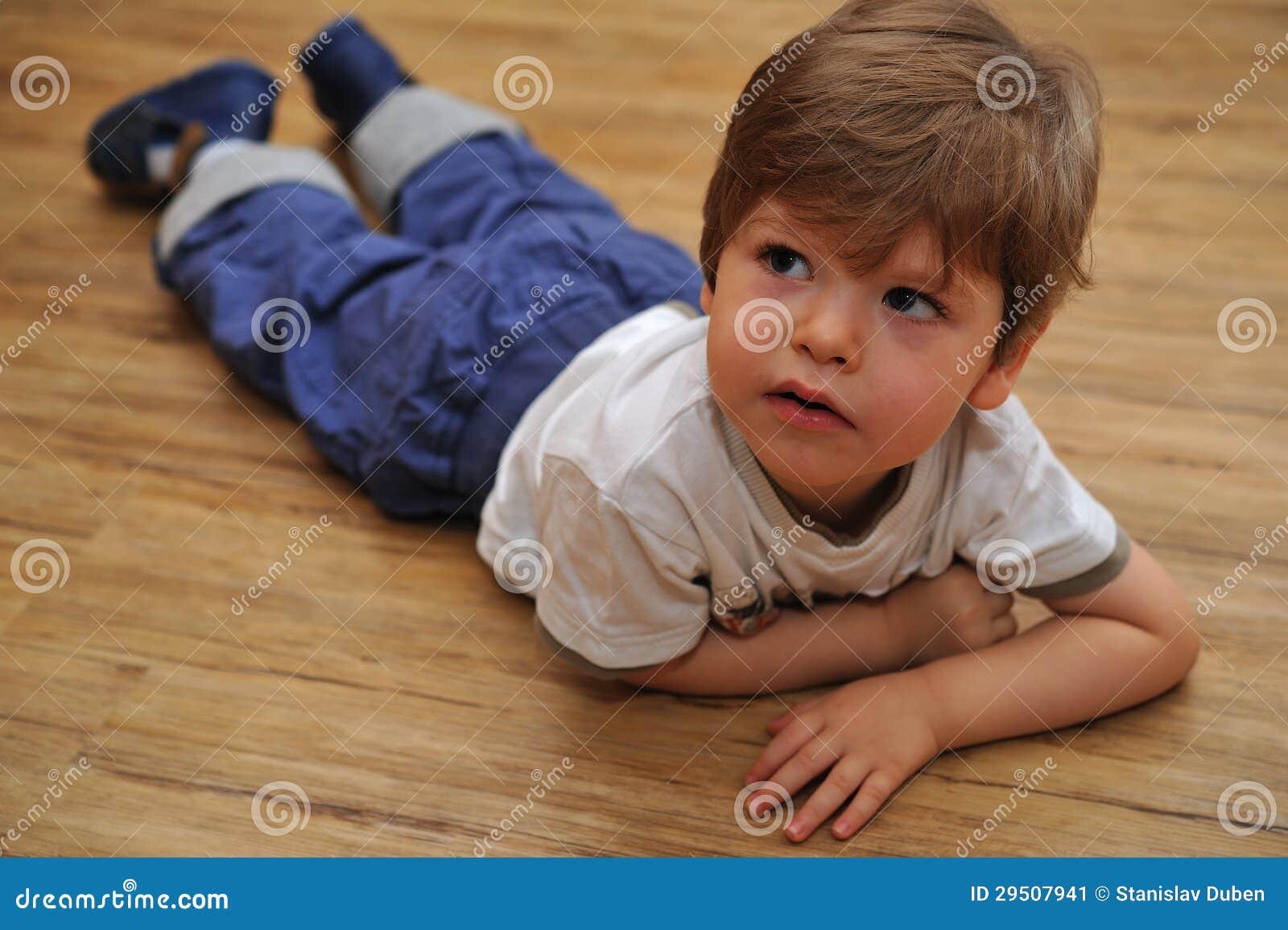 Nieuwsgierige kleine jongen die op houten vloer ligt