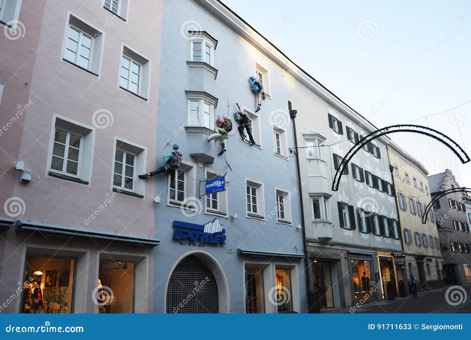 Nieuwsgierige voorgevelklimmer op een huisvoorzijde als winkel die in de Bruneck-voetgangers streek, Bruneck, Italië adverteren