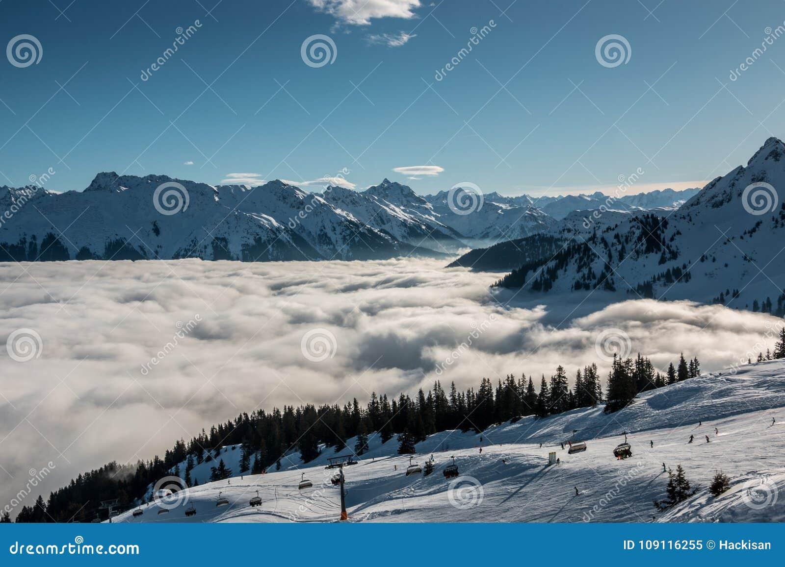 Nieve en el top de las montañas y de la niebla abajo del valle