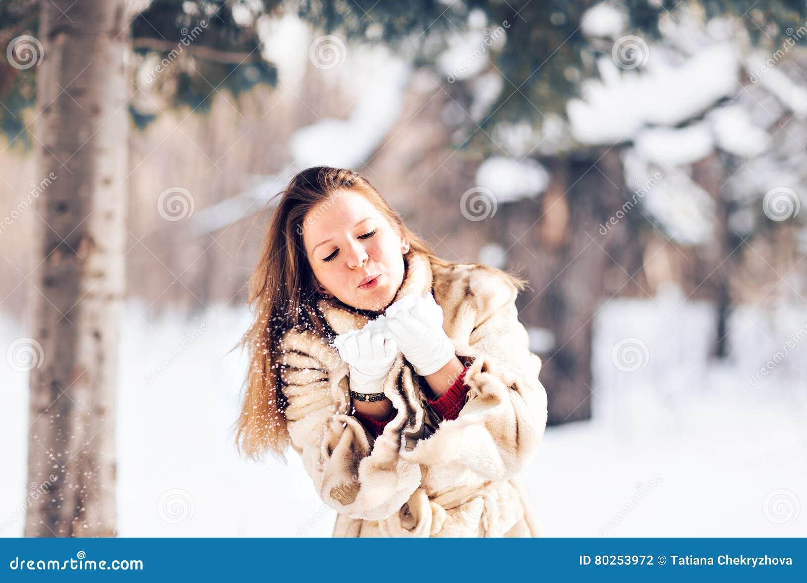 Nieve que sopla de la mujer hermosa joven en invierno