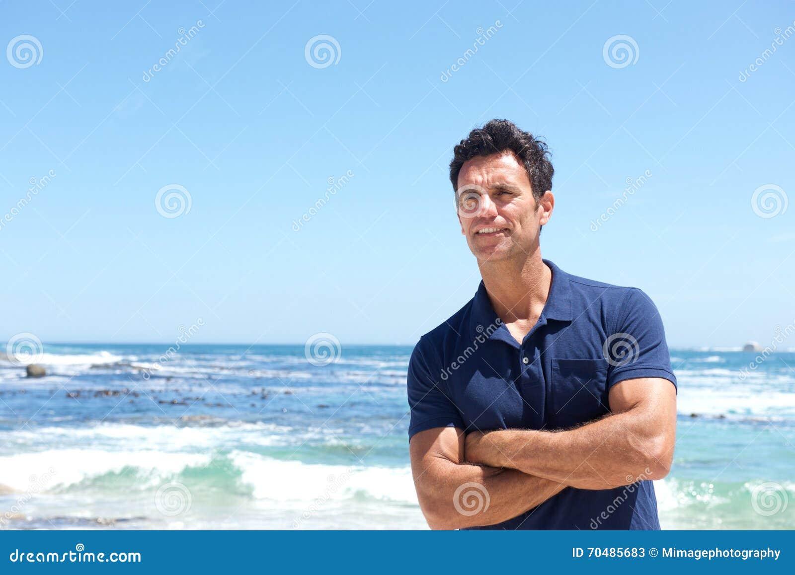Niewygładzona w średnim wieku mężczyzna pozycja przy plażą