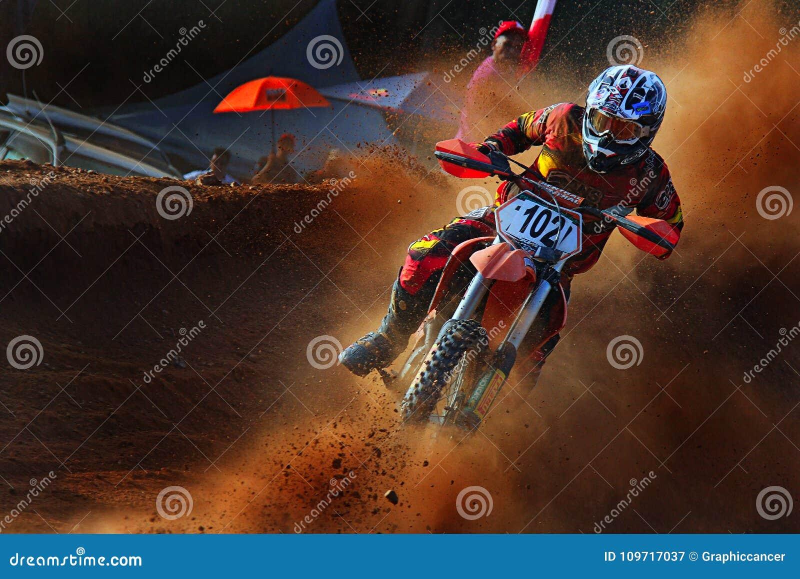 Niewygładzony motocyklu jeździec bierze ostrego zwrot w motocross turnieju