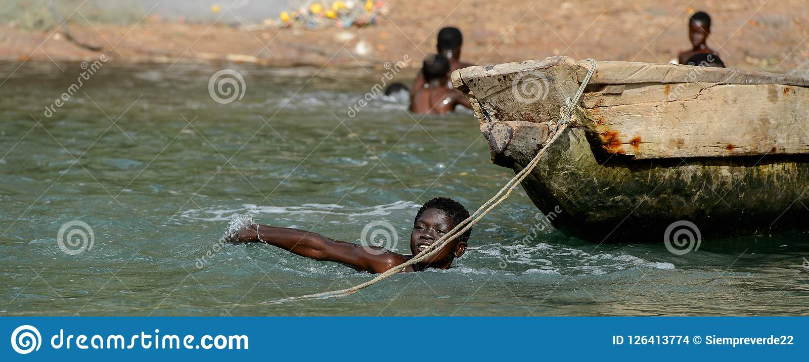 Niezidentyfikowana lokalna chłopiec pływa w wodzie podczas przypływu Obrazy Stock