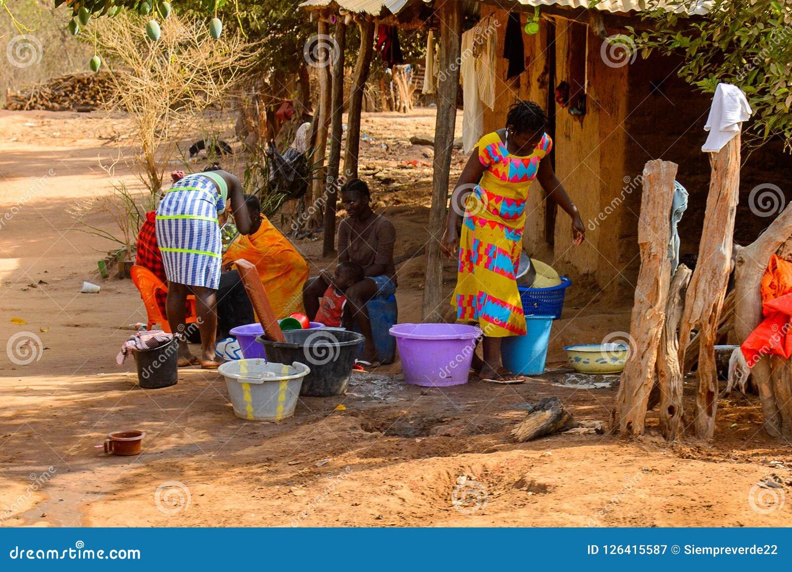Niezidentyfikowane lokalne kobiety myją odzieżowego w wiosce w gwinei Bi Fotografia Royalty Free