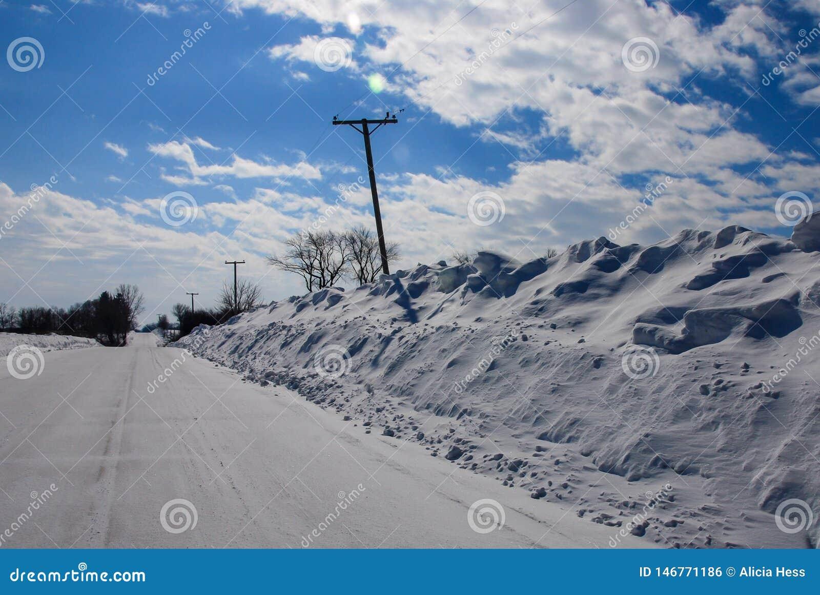 Niezwykle zgłębia snowbanks pchającego telefonicznego słupa zaginającego
