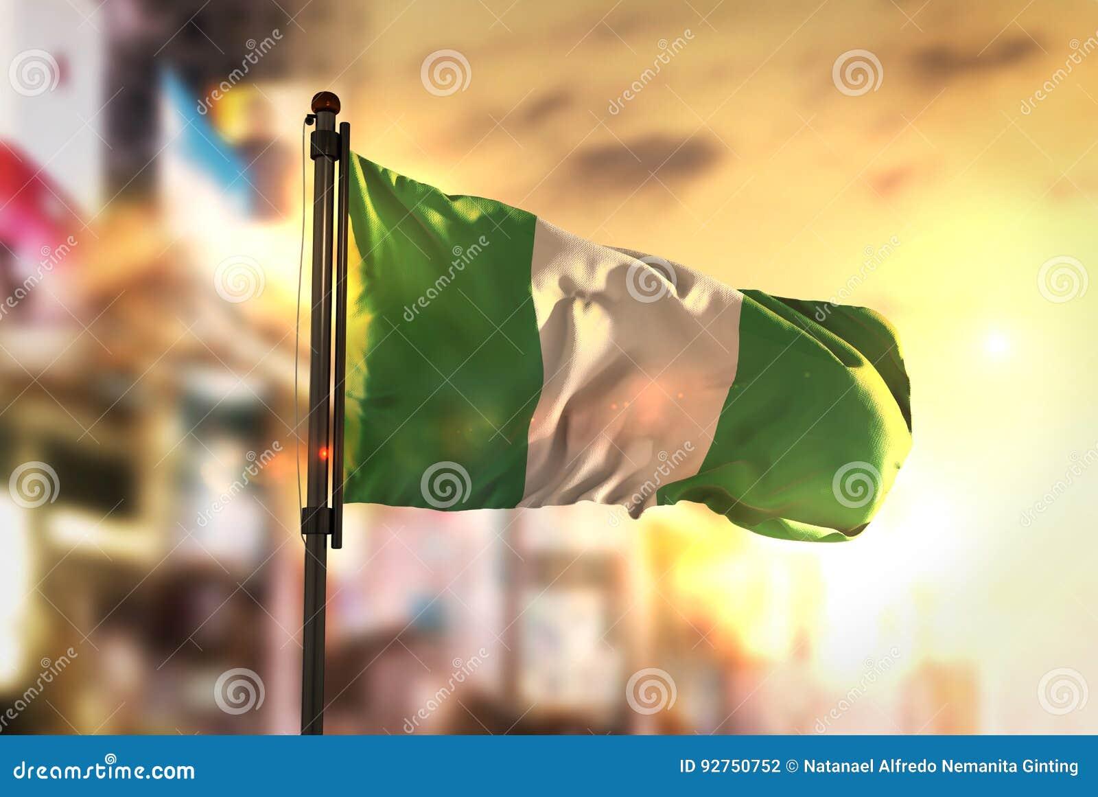 Nigeria-Flagge gegen Stadt unscharfen Hintergrund bei Sonnenaufgang Backligh