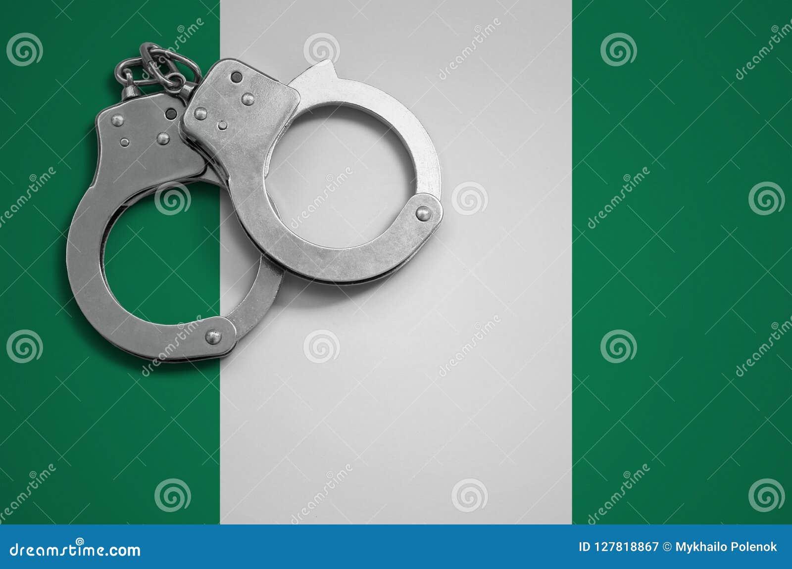 Nigeria-Flaggen- und -polizeihandschellen Das Konzept des Verbrechens und der Handlungen im Land