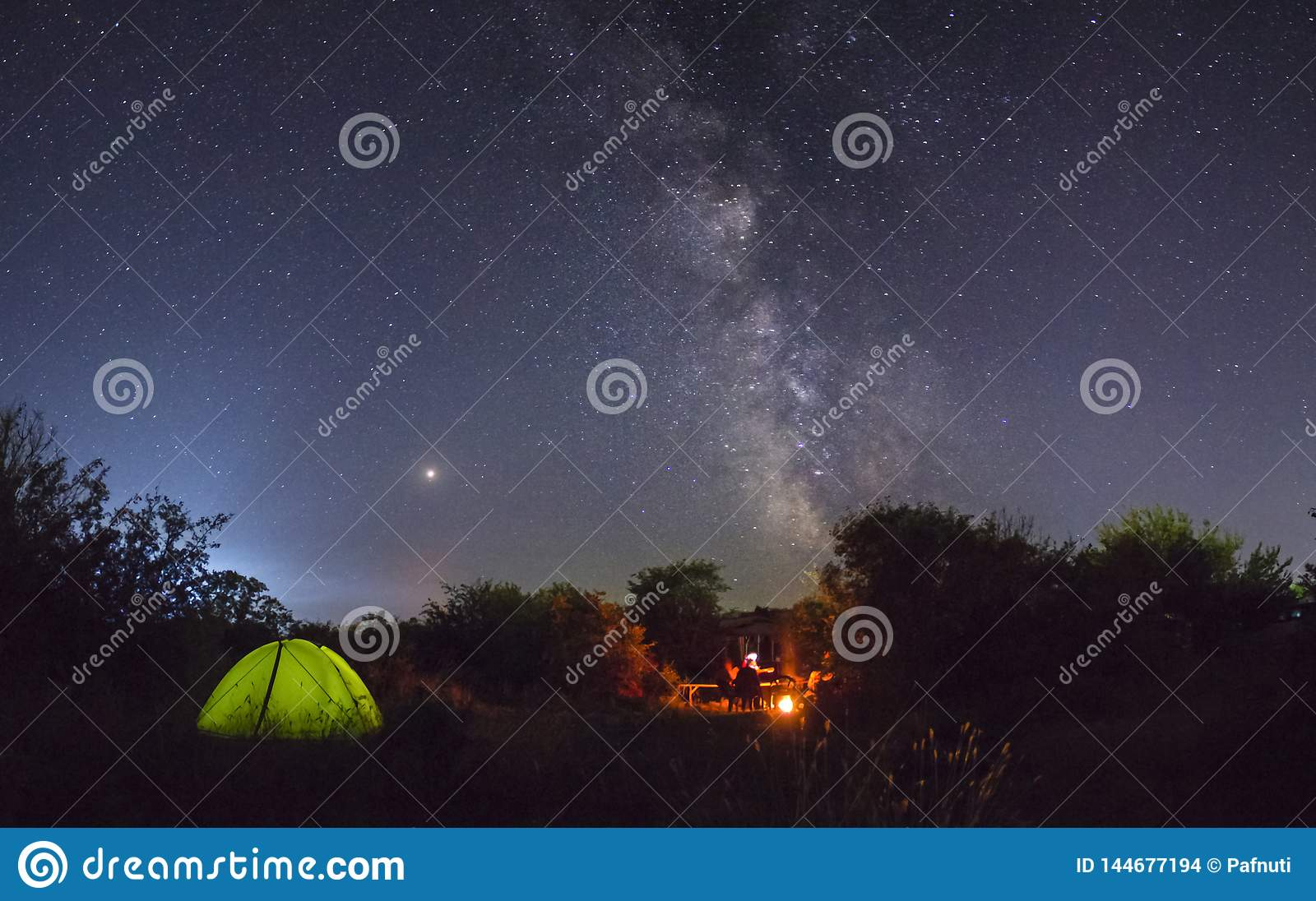 Night camping. Couple tourists have a rest at a campfire near illuminated tent under amazing night sky