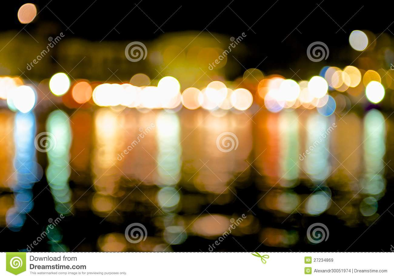 Coastal City Night Lights Reflected In The Dark Sea Water And Break Up A  Lot Of Bright, Colorful Highlights.