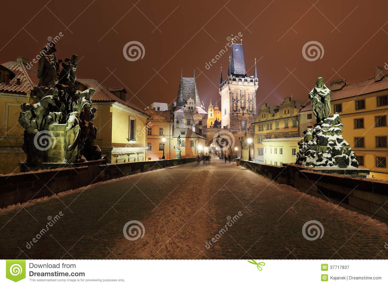 Night colorful snowy Prague bridge Tower with Sculptures from the Charles Bridge