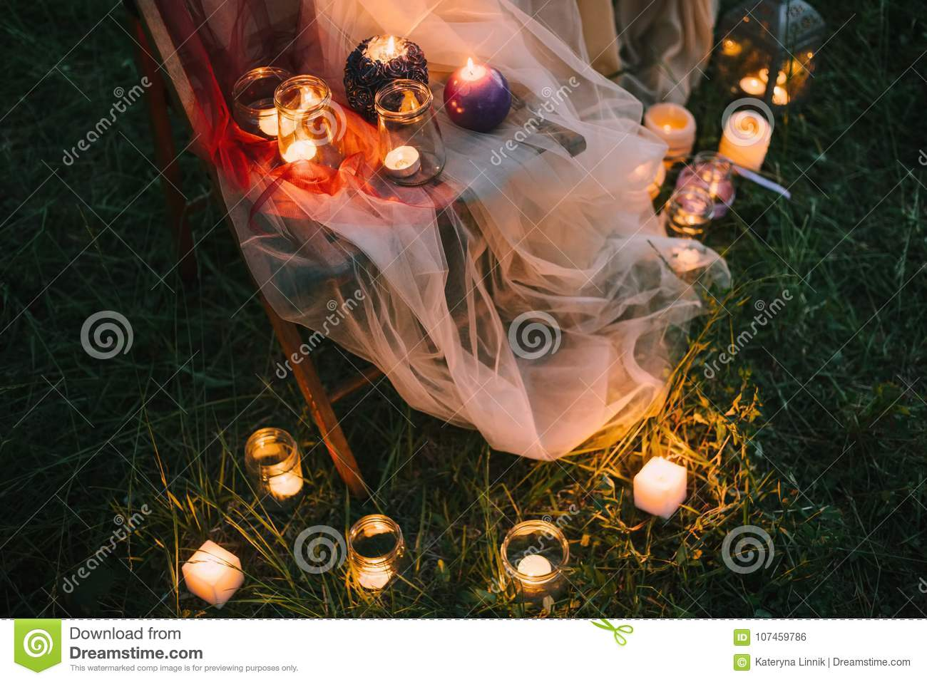 Night fine art outdoor wedding details: summer or spring ceremony with decor lowlight candles standing on chair covered