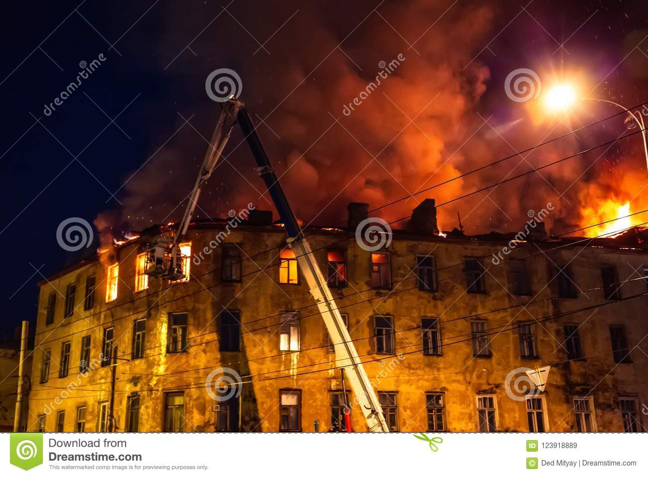 night fire at roof in apartment building burning house with huge