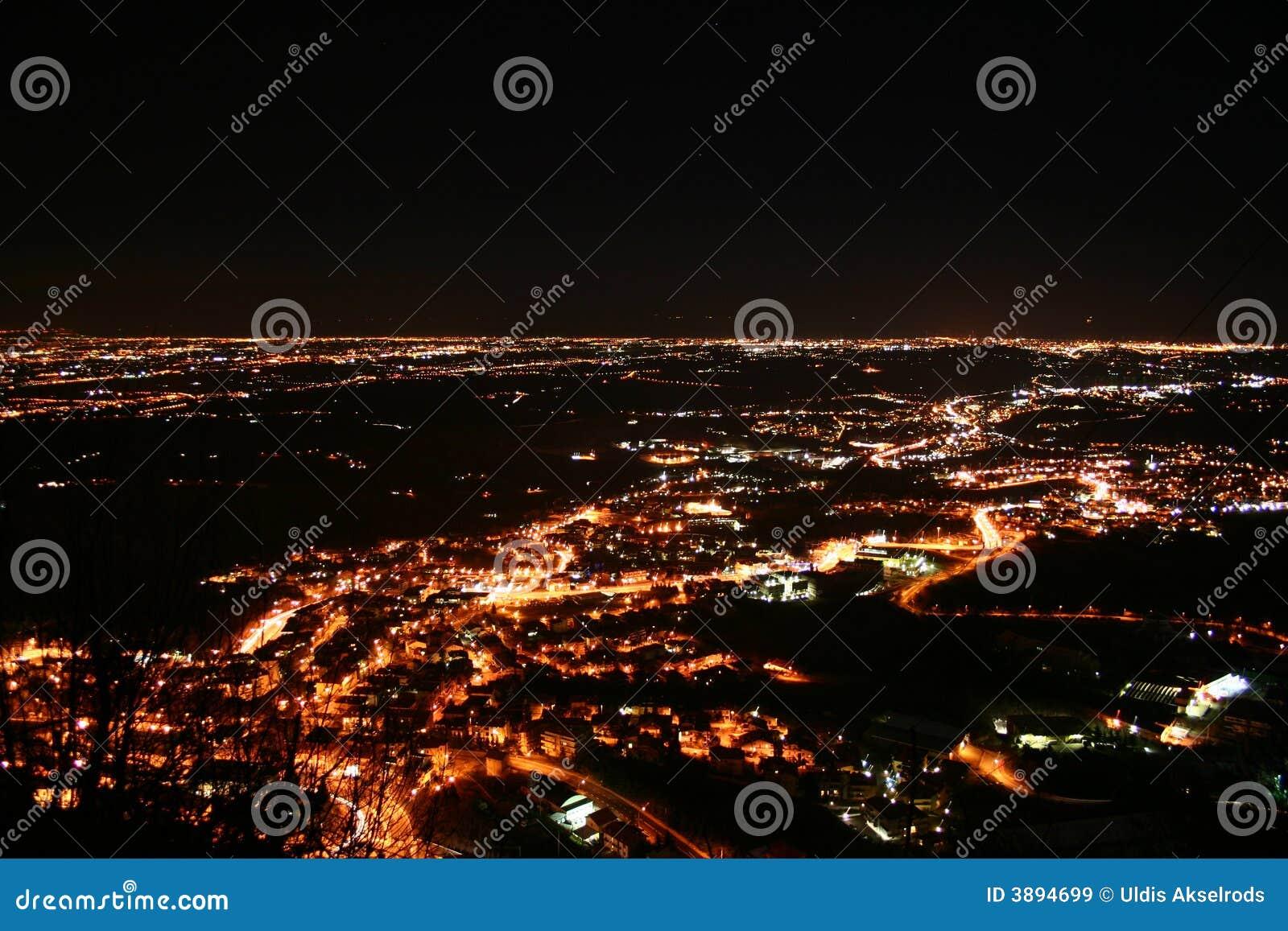 Night flight city lights in a valley
