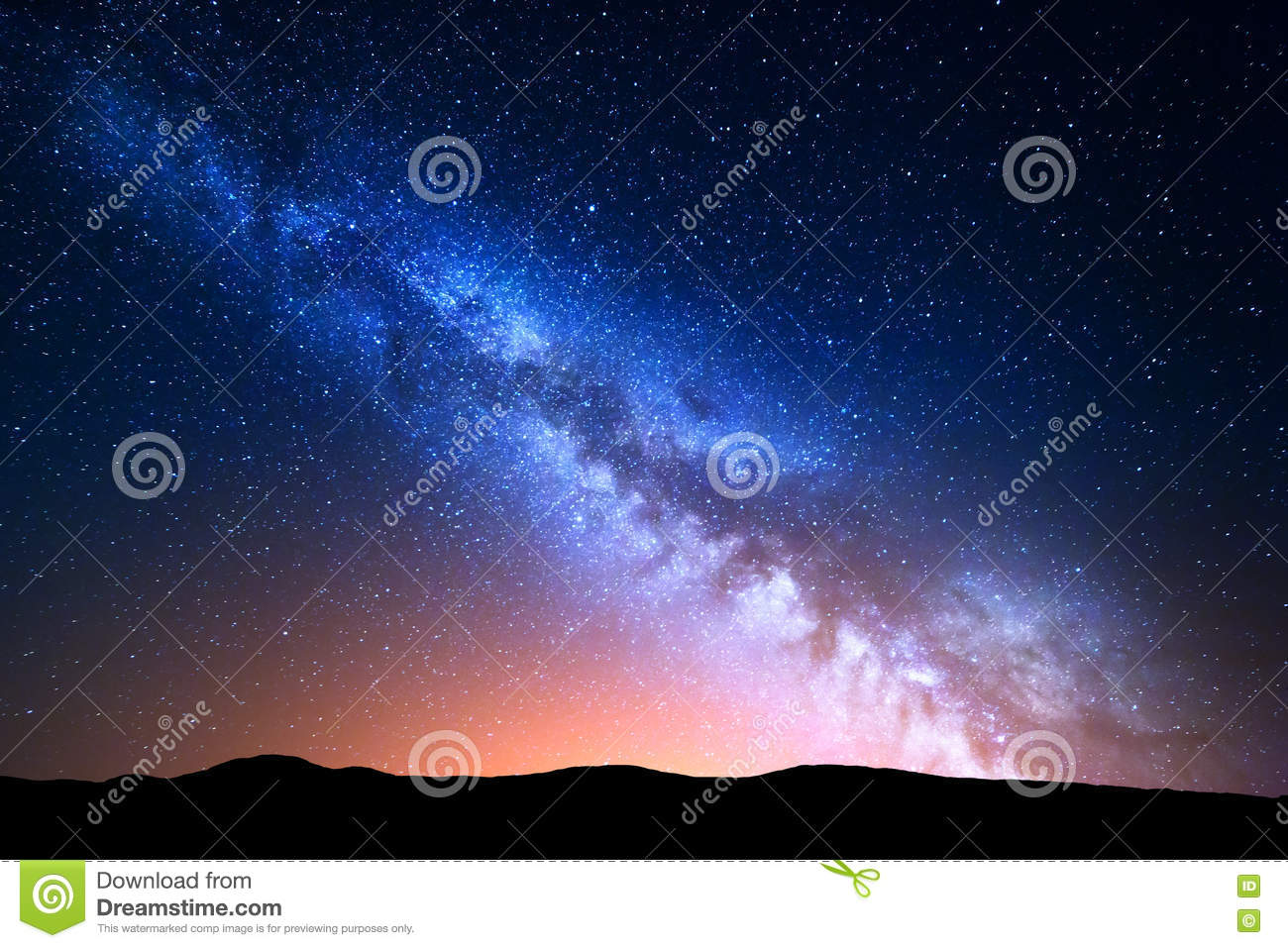 Night landscape with colorful Milky Way and yellow light at mountains. Starry sky with hills at summer. Beautiful Universe. Space
