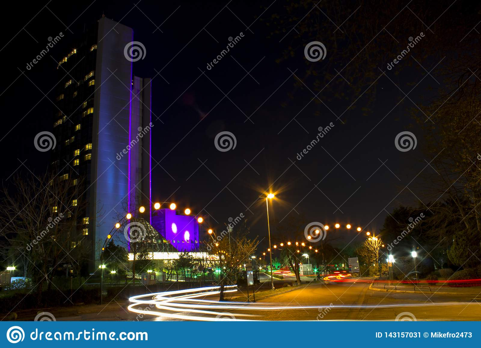 Night landscape on long exposure. Tall building and cars passing the night lights