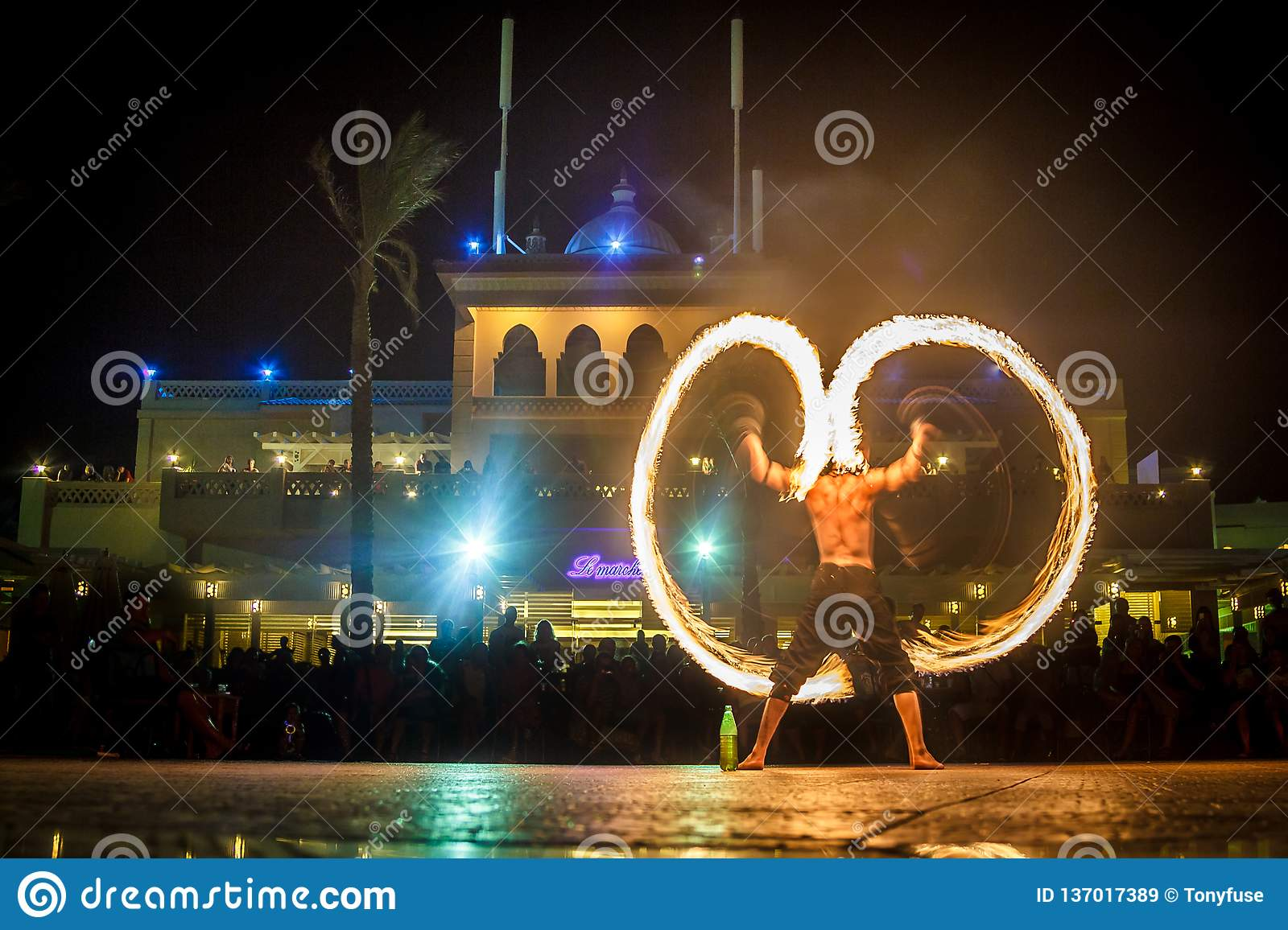 Night performance fire show in front of a crowd of people