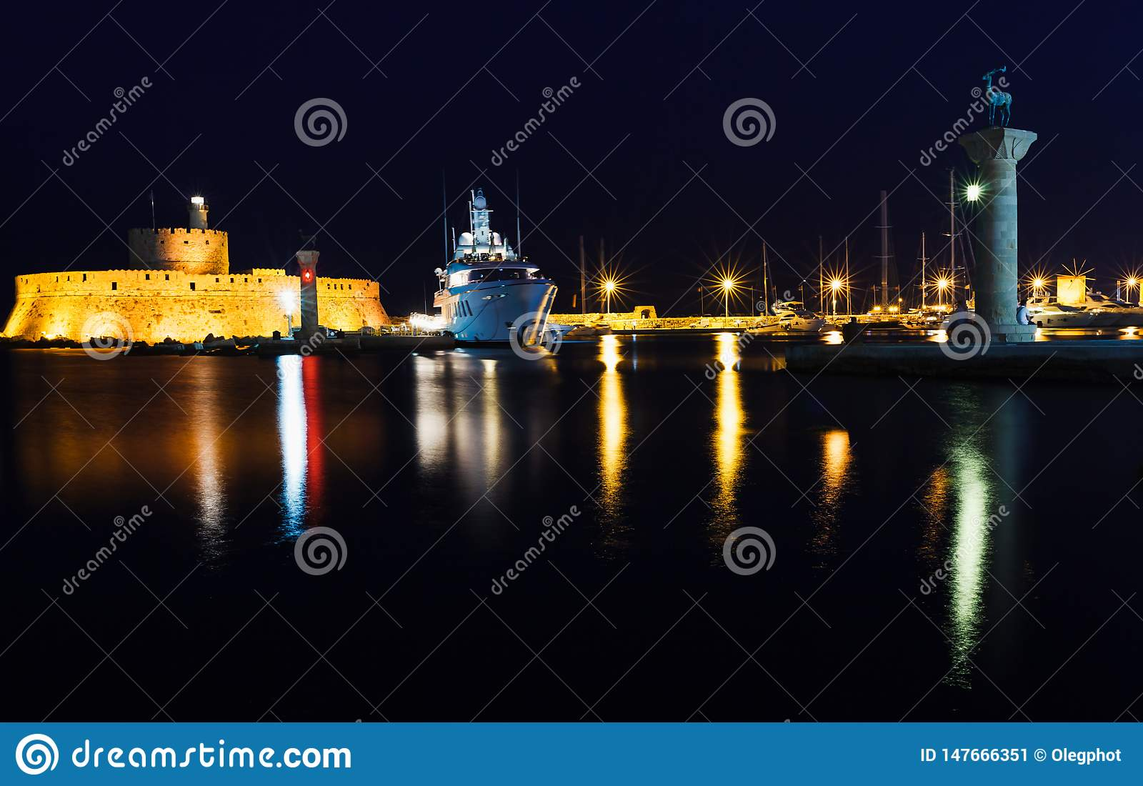 Night photo of ancient fortress and pier in Rhodes city on Rhodes island, Dodecanese, Greece. Stone walls and bright night lights