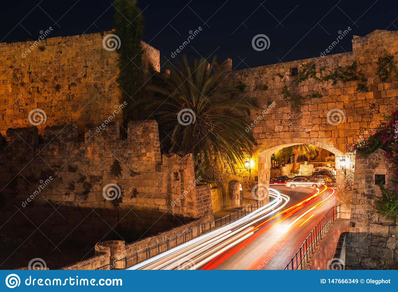 Night photo of ancient street in Rhodes city on Rhodes island, Dodecanese, Greece. Stone walls and bright night lights. Famous