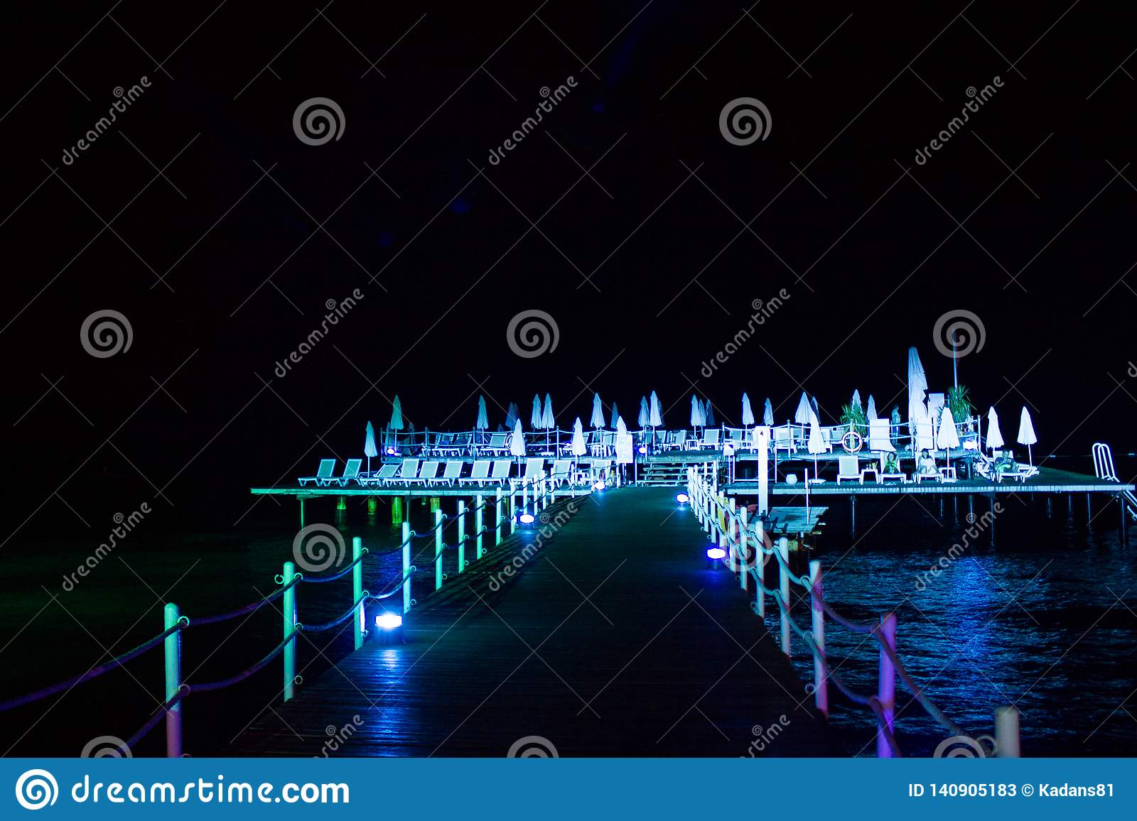 Night pier with sun loungers, in bright lights, on the sea