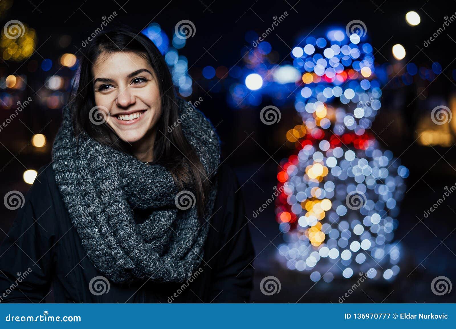 Night portrait of a beautiful brunette woman smiling enjoying winter in park.Winter joy.Winter holidays.Positive emotions.