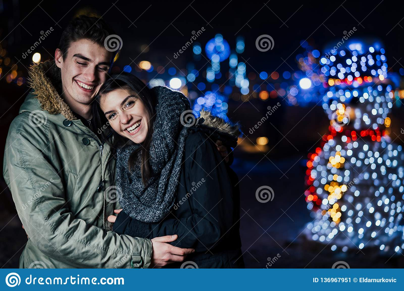 Night portrait of a happy couple smiling enjoying winter and snow aoutdoors.Winter joy.Positive emotions.Happiness