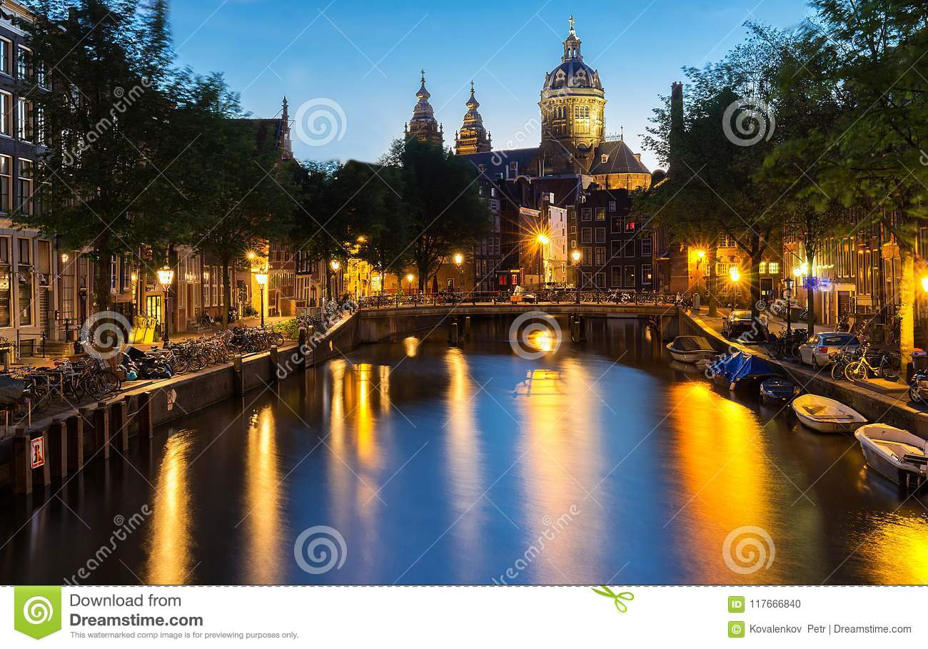 Night red-light district De Wallen, canal, Basilica of Saint Nicholas and bridge, Amsterdam, Holland. Long exposure.