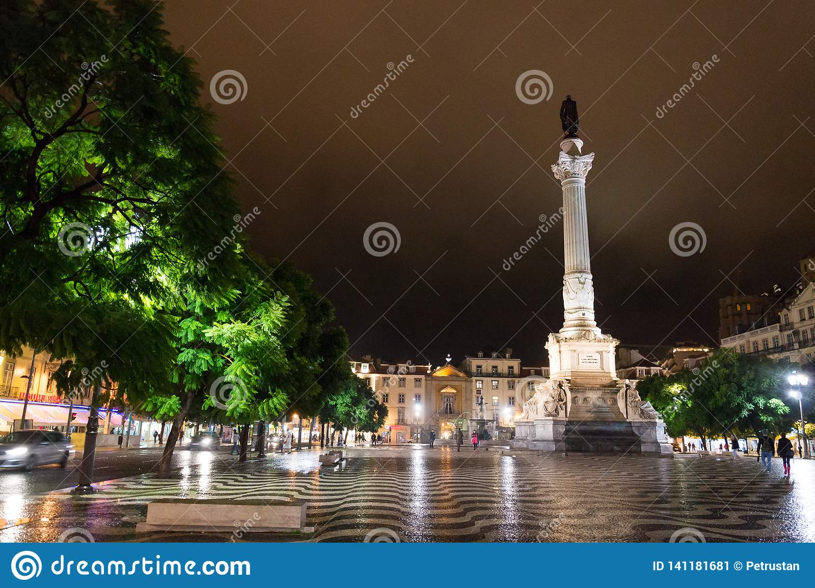 Night scene of Rossio Square, Lisbon, Portugal with one of its decorative fountains and the Column of Pedro IV