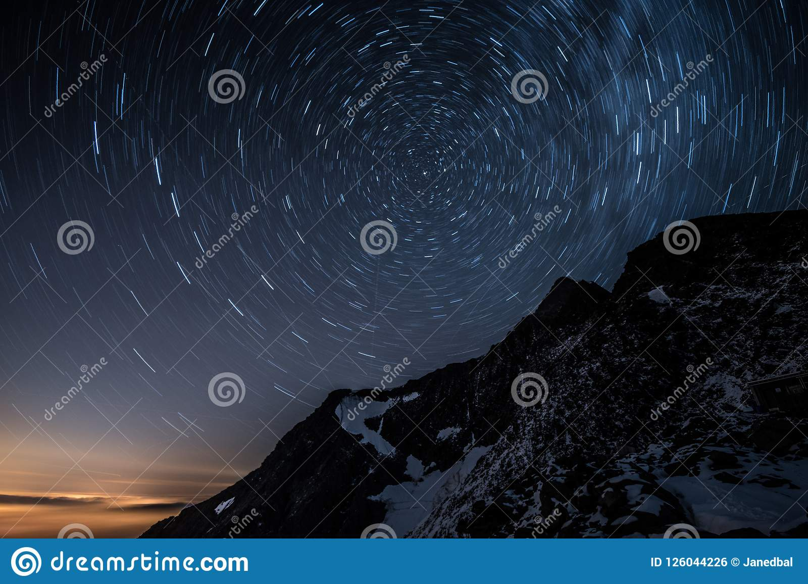 Night sky star trails above Aiguille de Bionnassay mountain, Alps, France