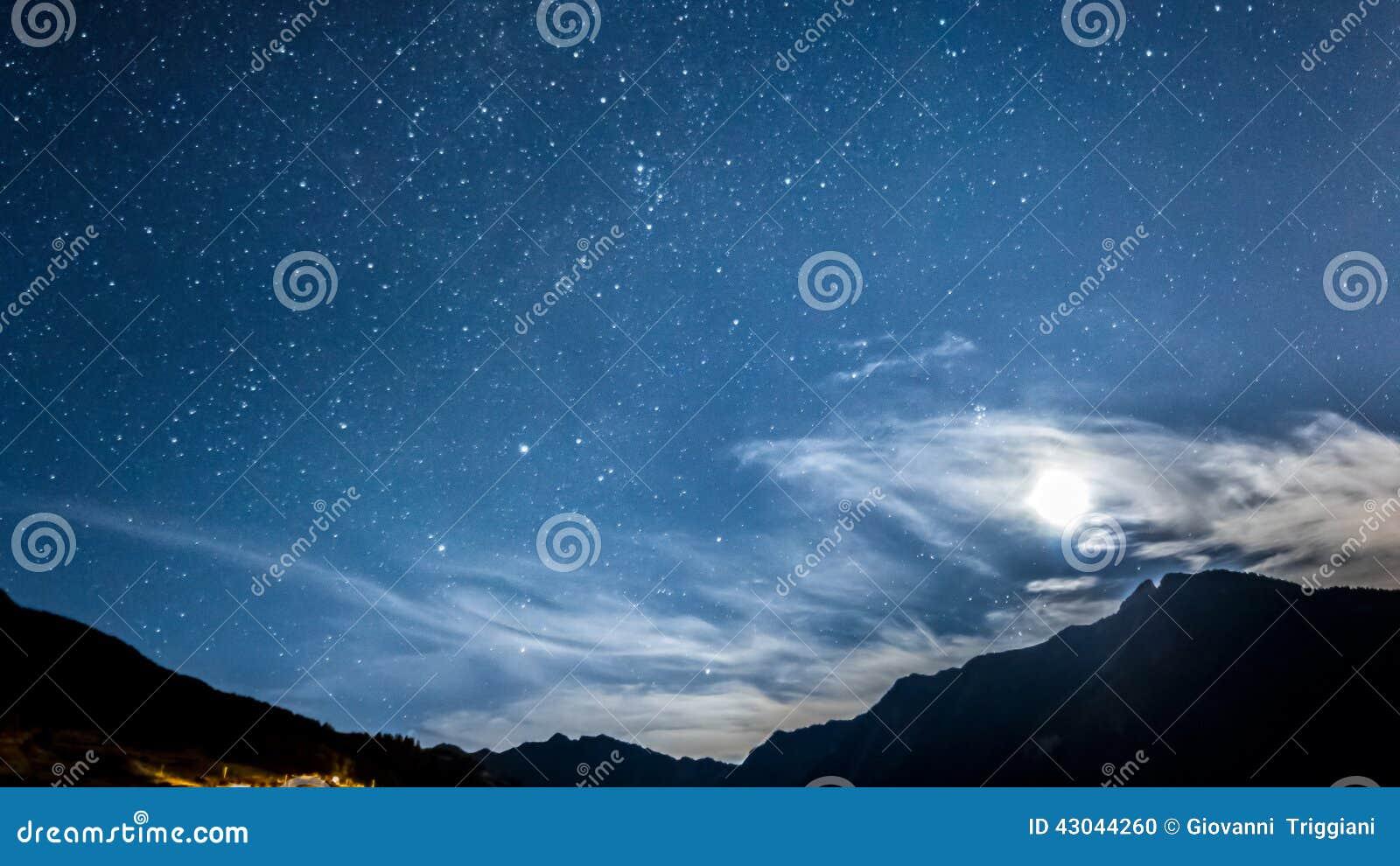 Night sky stars and moon across mountain